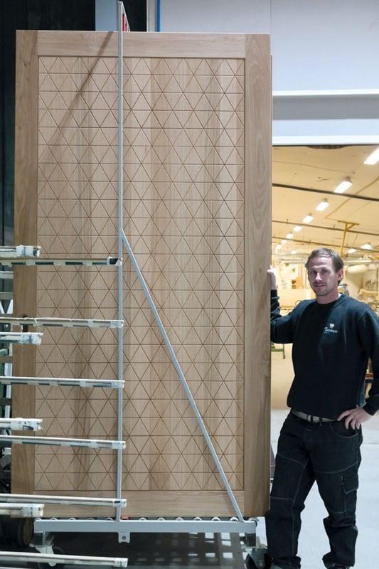 Daglig leder Tommy Pettersen viser fram en av dørene som snart er klar til levering.
